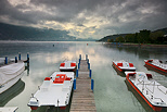 Photo of Annecy lake under a cloudy sky by an autumn morning