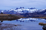 Image of Aiguilles d'Arves mountains partially covered in snow and their reflection on lake Guichard