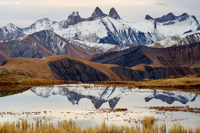 Image of Aiguilles d'Arves mountains reflected on the water of lake Guichard
